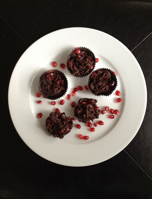 Chocolate pomegranate clusters on a white plate
