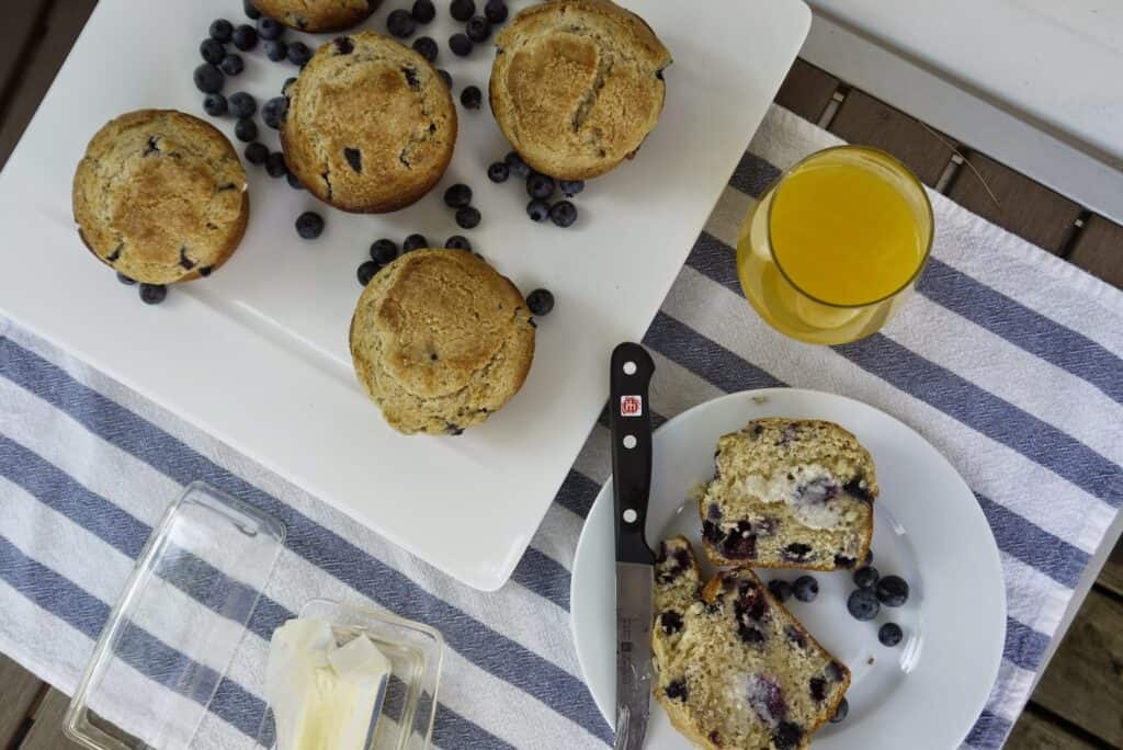 5 large blueberry muffins on a white plate with fresh blueberries and one sliced with butter