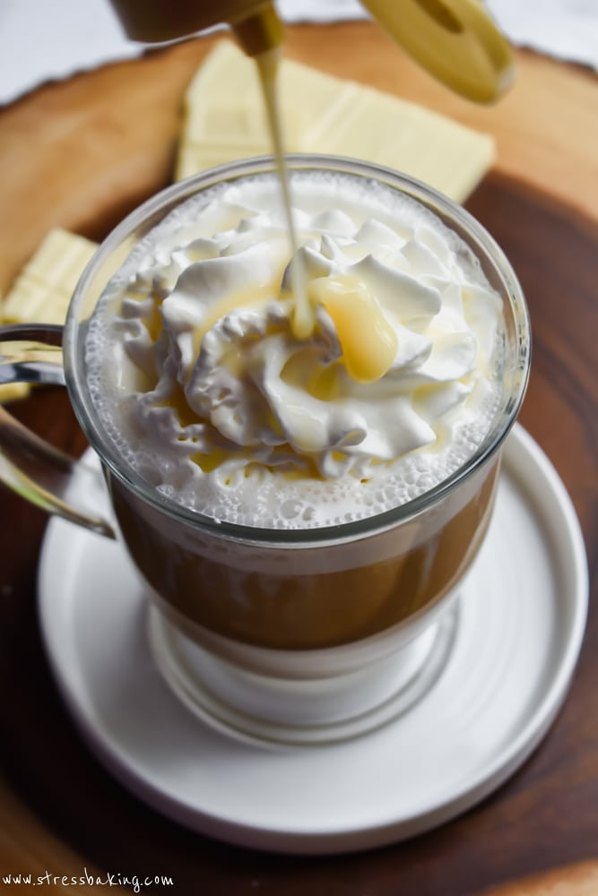 White chocolate syrup being poured on top of white chocolate mocha topped with whipped cream in a clear mug