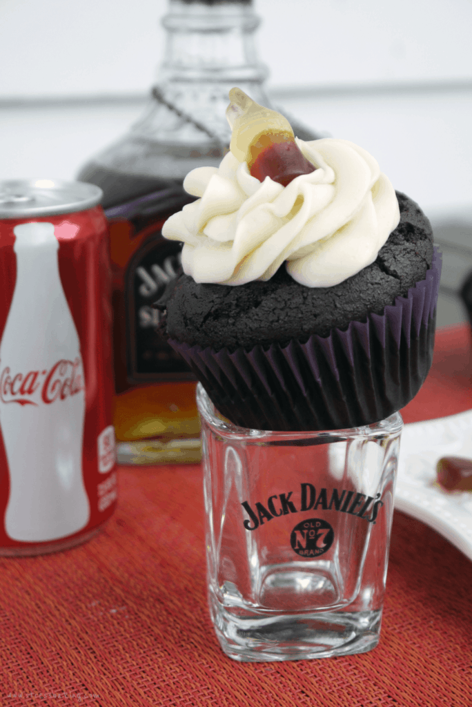 Chocolate cupcake topped with a swirl of buttercream frosting and topped with a candy coke bottle sitting on top a Jack Daniel's shot glass