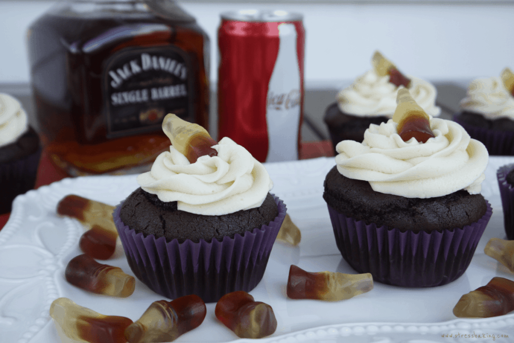 Chocolate cupcakes topped with a swirl of buttercream frosting and topped with candy coke bottles next to a bottle of Jack Daniels and Coca Cola