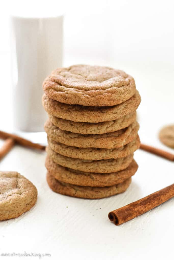 A stack of snickerdoodles next to a glass of milk on a white counter