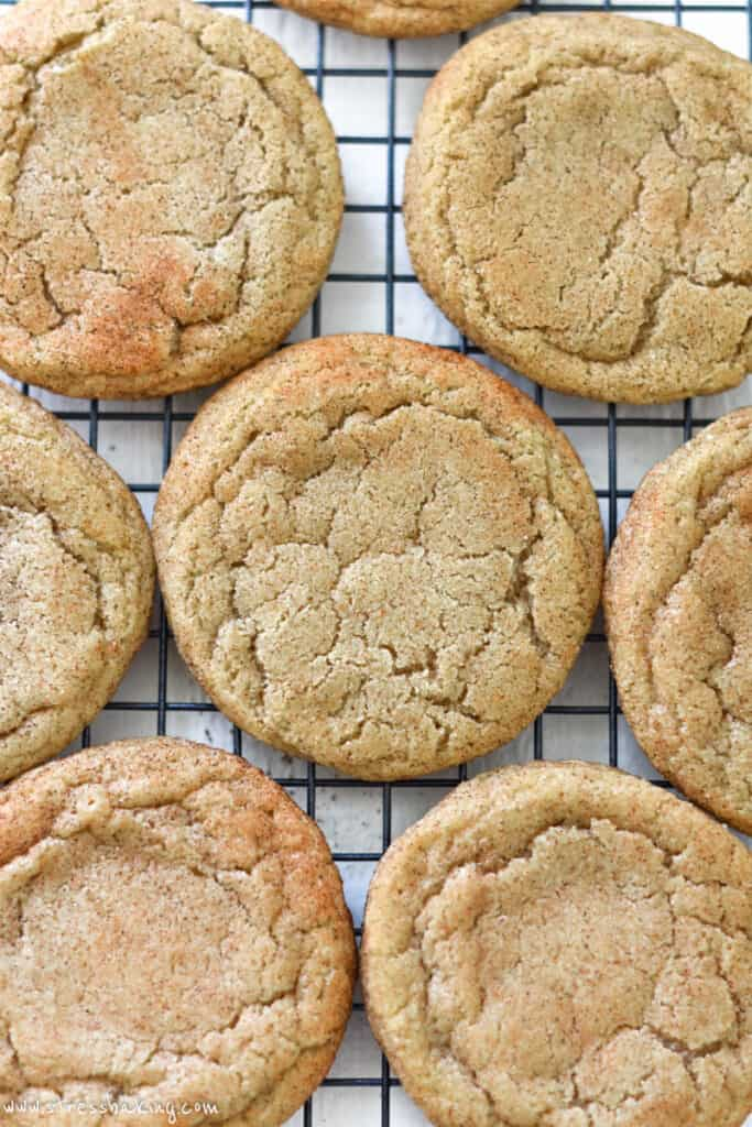 Close up of the crinkled tops of snickerdoodle cookies on a wire rack