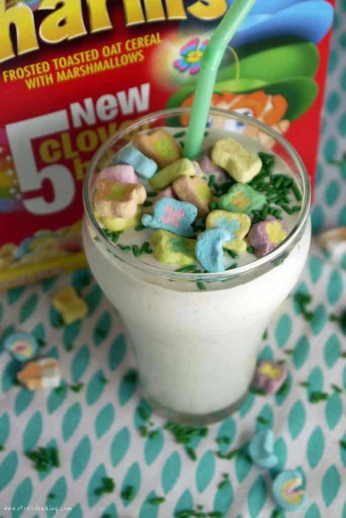 A milkshake topped with marshmallow cereal pieces in front of a red Lucky Charms box