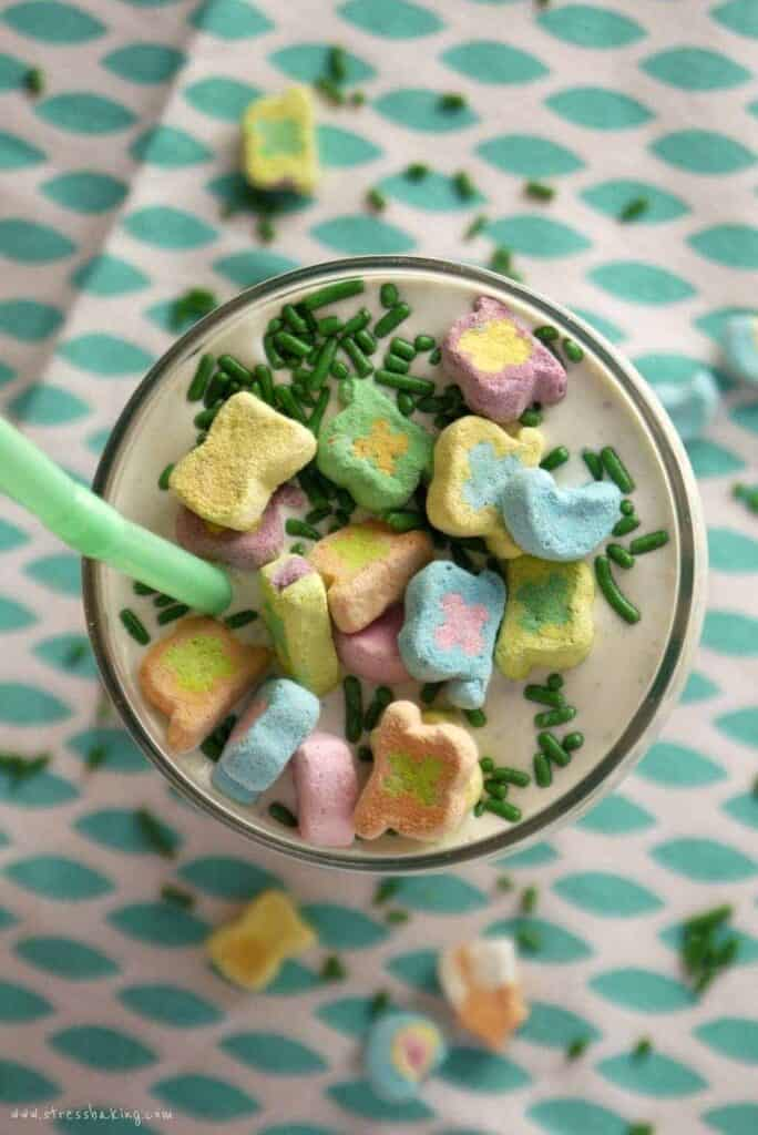 Overhead shot of a milkshake topped with marshmallow cereal pieces and green sprinkles