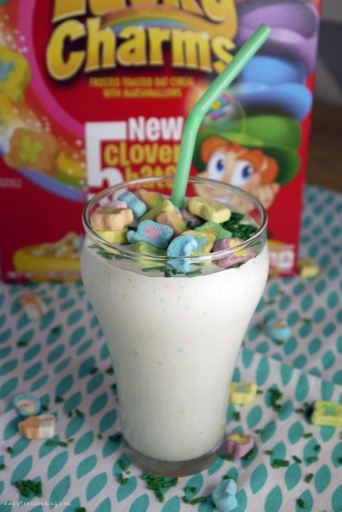 A milkshake with a green straw topped with marshmallow cereal pieces in front of a red Lucky Charms box
