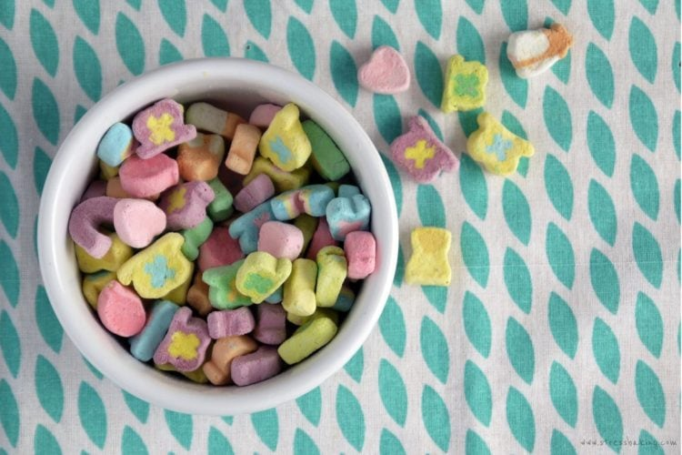 A small white bowl overflowing with Lucky Charms marshmallow cereal pieces