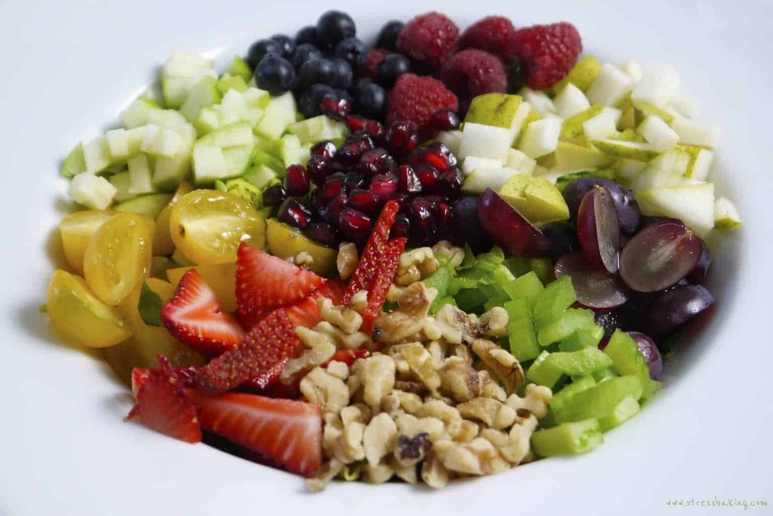 All the fruits and vegetables for salad chopped in a white bowl