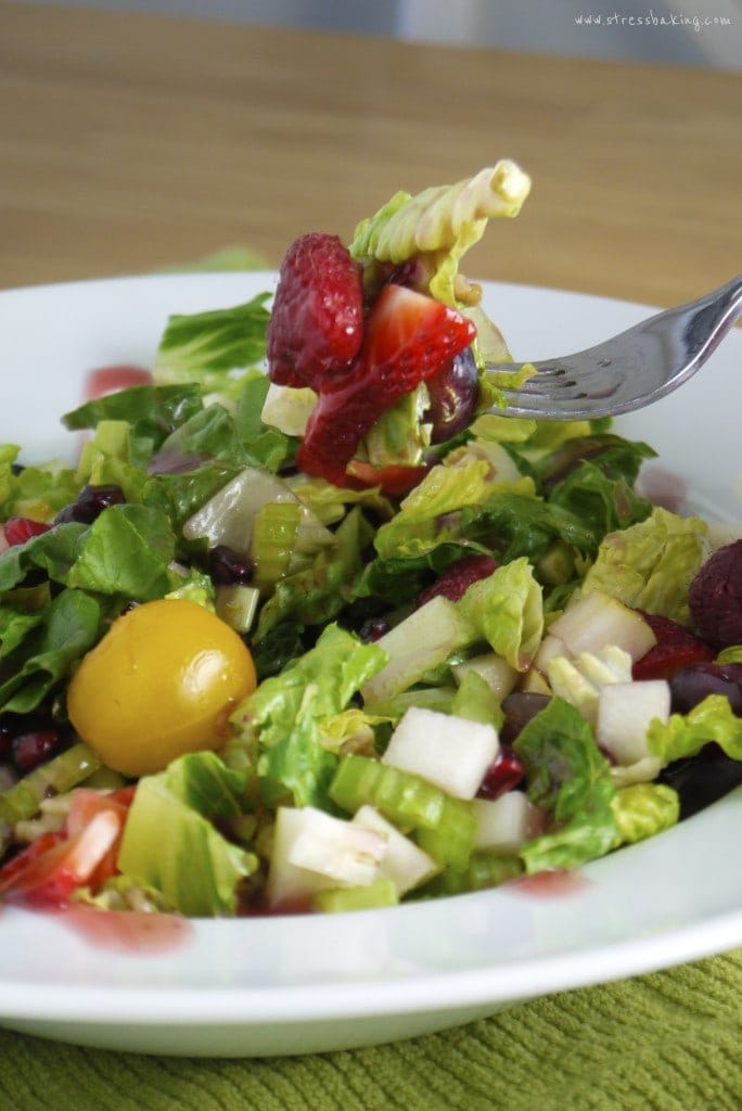 A forkful of a colorful spring salad in a white bowl