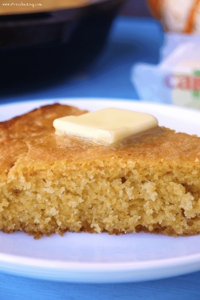 A slice of cornbread with a melty tab of butter