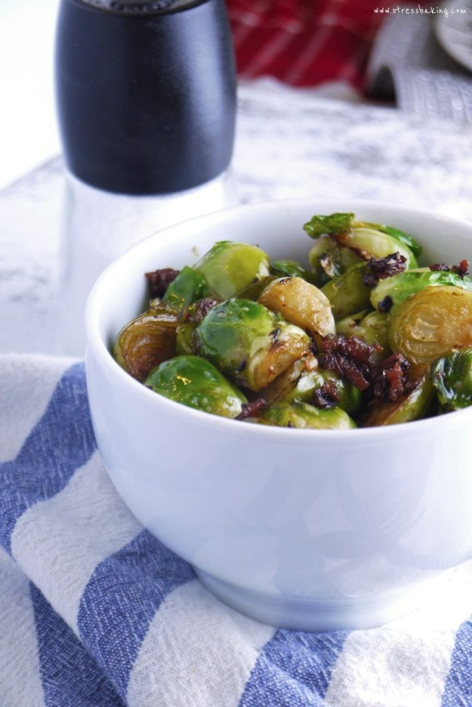Fried brussels sprouts with crumbled bacon in a white bowl