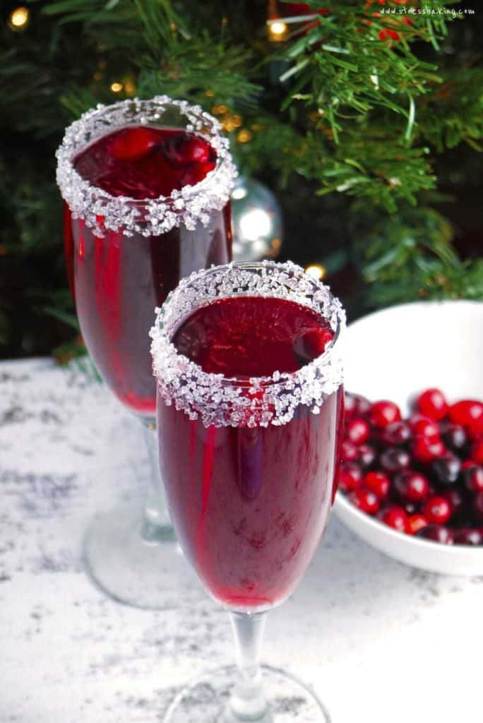 Two glasses of cranberry mimosa in front of a Christmas tree with sugared rims