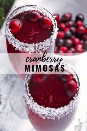 Cranberry Mimosas rimmed with sugar and topped with fresh cranberries next to a bowl of fresh cranberries
