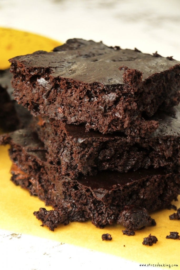 Fudgy Chocolate Banana Brownies stacked on top of parchment paper with a banana