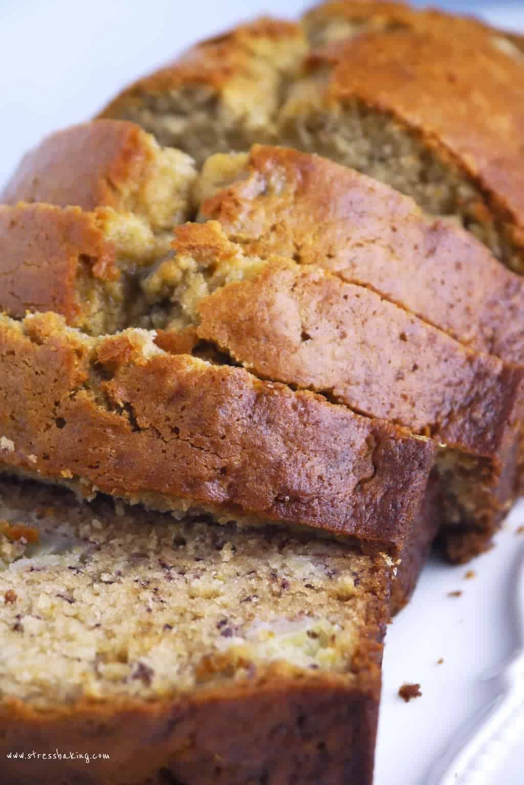 A loaf of golden banana bread, sliced on a white plate
