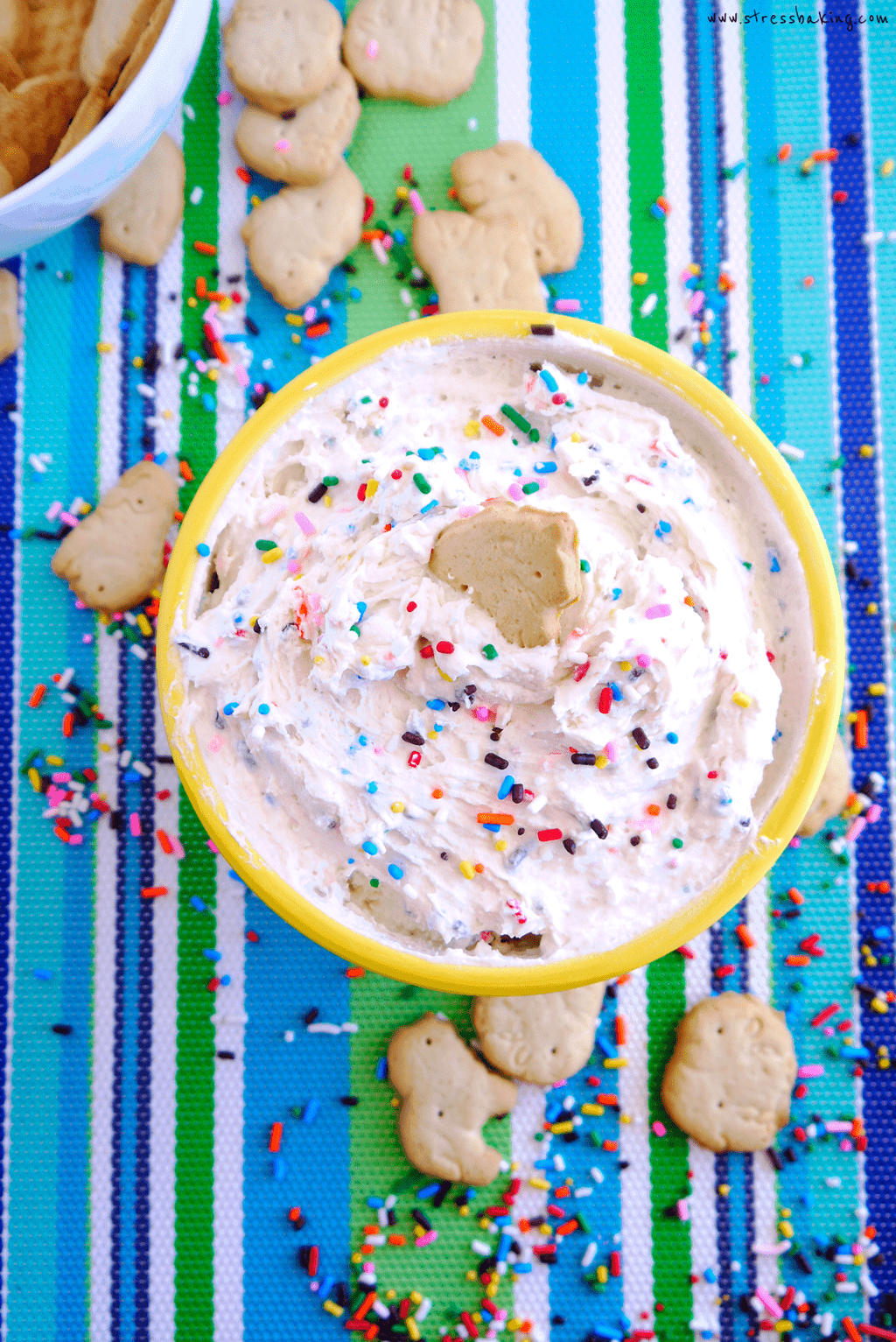 Yellow bowl full of funfetti dunkaroo dip topped with sprinkles on a colorful striped placemat with animal crackers