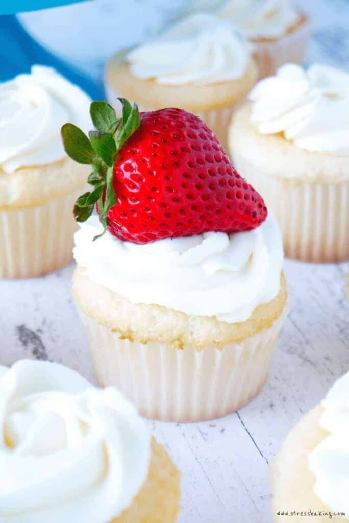 Boozy Angel Food Cupcakes with Amaretto Soaked Strawberries on a white piece of wood