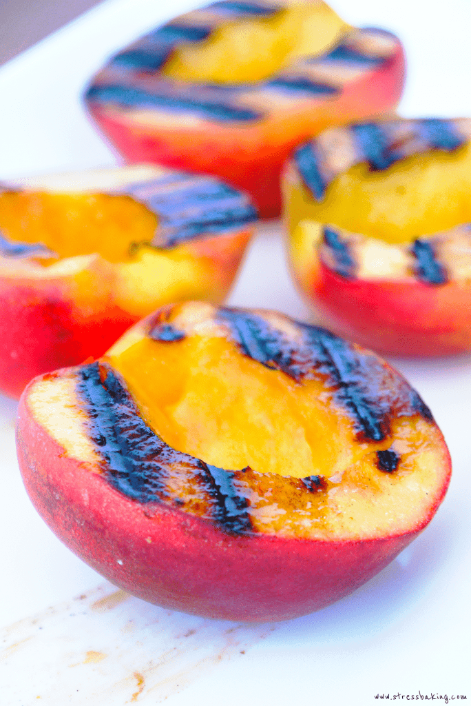 Grilled peaches on a white platter