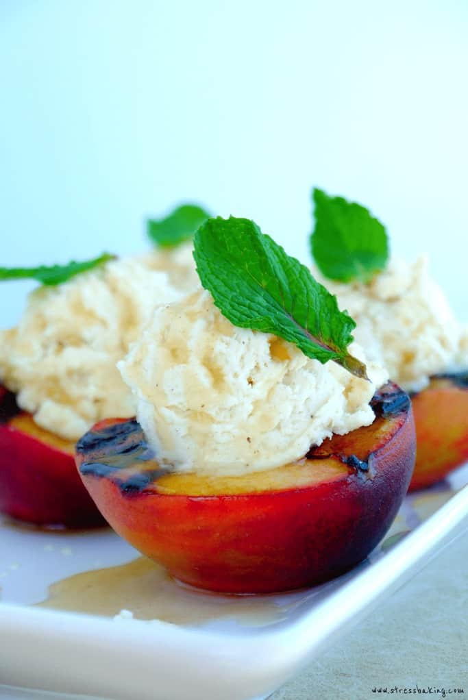 Grilled peach topped with whipped cream and a mint leaf on a white platter