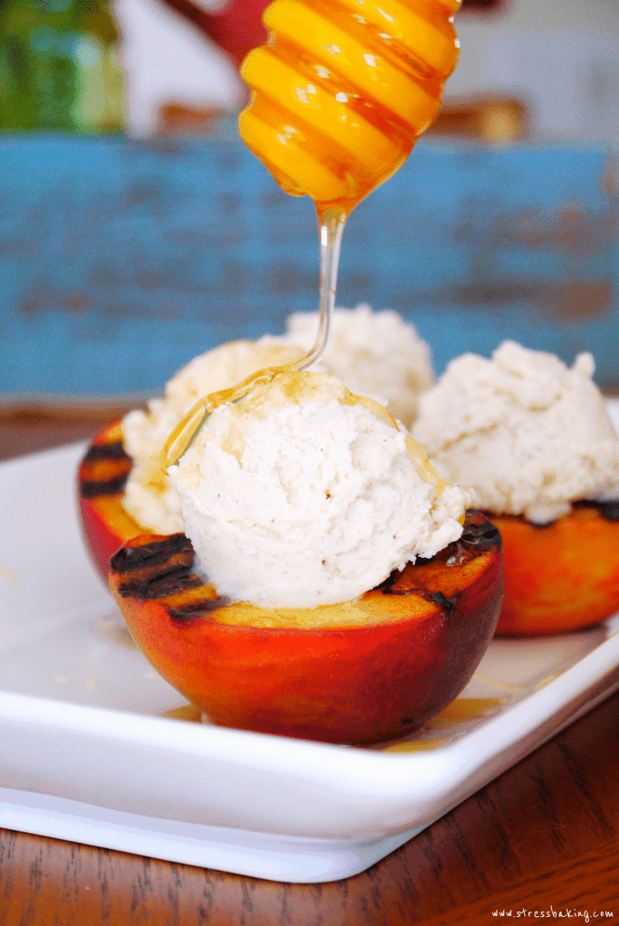 Grilled Peaches with Cinnamon Mascarpone Whipped Cream being drizzled with honey