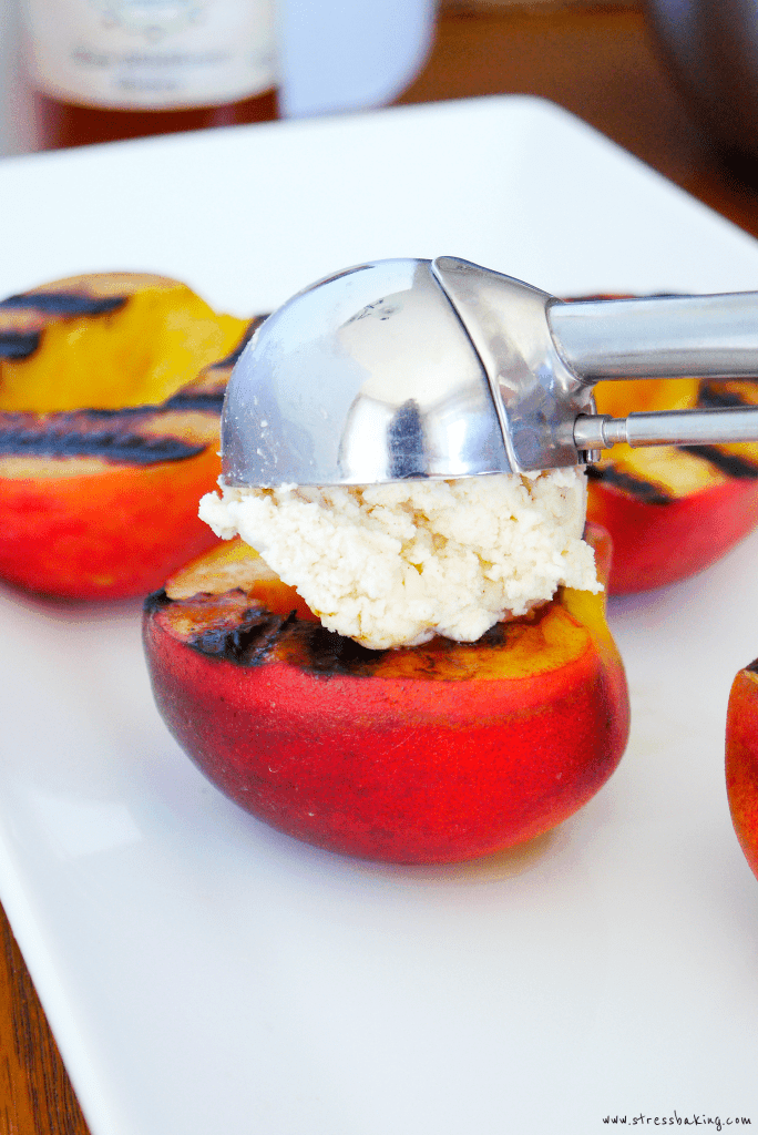 Grilled peaches being topped with a scoop of cinnamon mascarpone