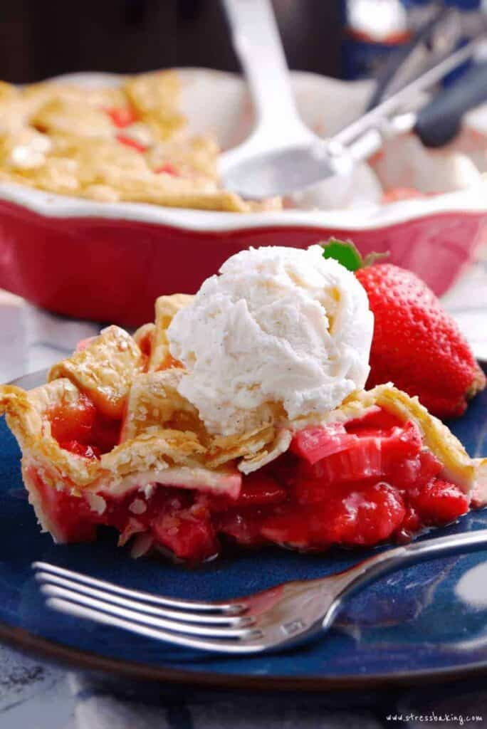 A slice of strawberry rhubarb pie topped with vanilla ice cream on a blue plate