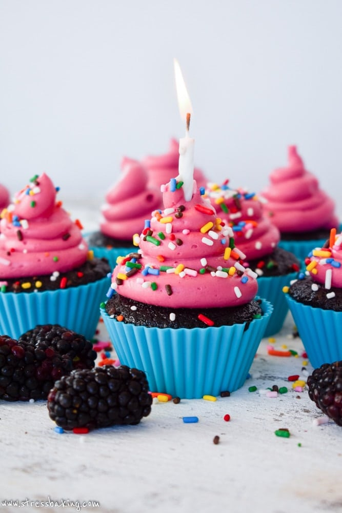 Red Wine Chocolate Cupcakes with Pink Blackberry Buttercream Frosting and rainbow sprinkles with a birthday candle