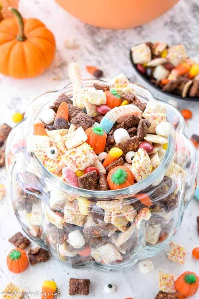 Halloween Puppy Chow: Whether you call it puppy chow or muddy buddies, the addition of Halloween candy and autumn colors turn this into the perfect festive party snack! | stressbaking #stressbaking #halloween