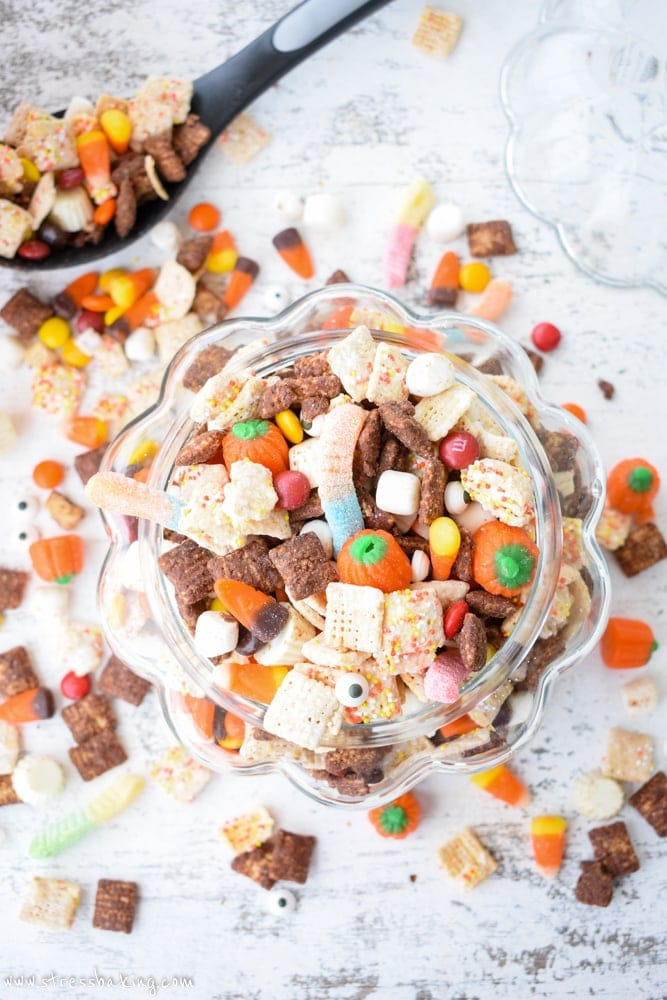 Overhead shot of colorful Halloween puppy chow in a glass pumpkin on a white wooden background