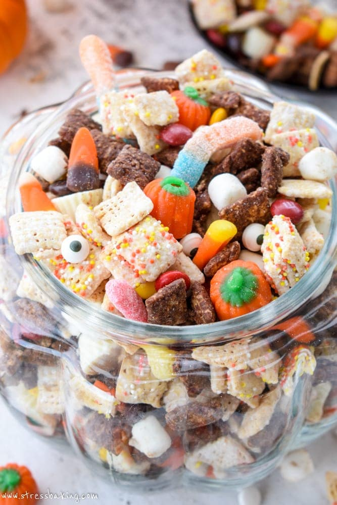 Closeup of colorful Halloween puppy chow in a glass pumpkin on a white wooden background
