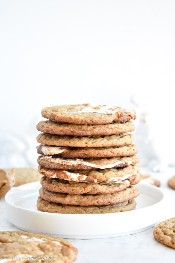 Side shot of a stack of peanut butter cookies with marshmallow swirls on a white plate