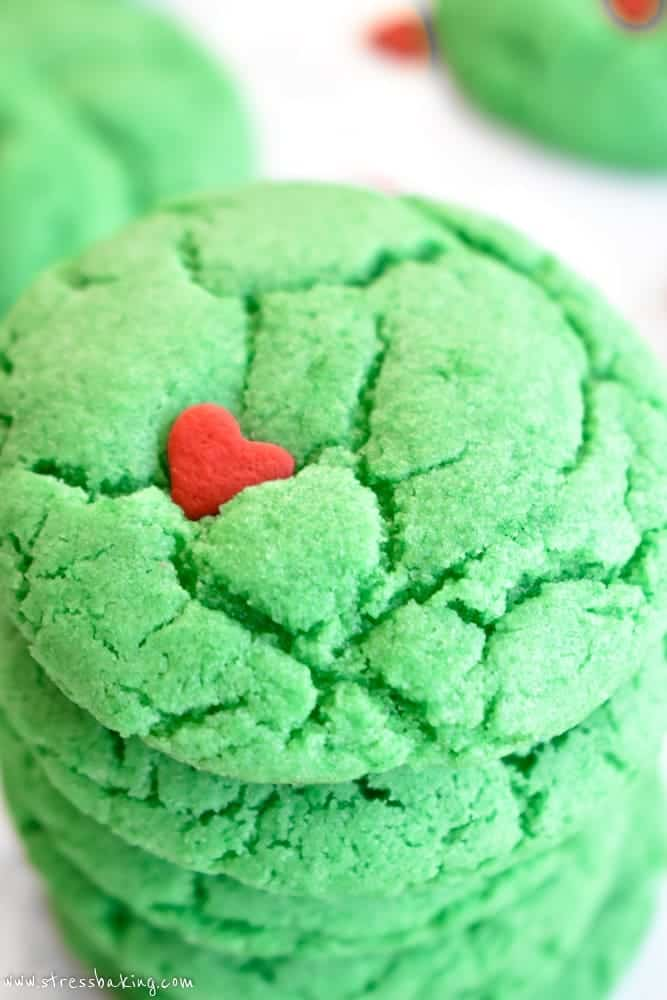 Close up of stack of vibrant green Grinch cookies with red heart sprinkles