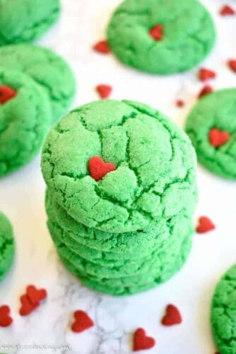 A stack of vibrant green Grinch cookies with red heart sprinkles