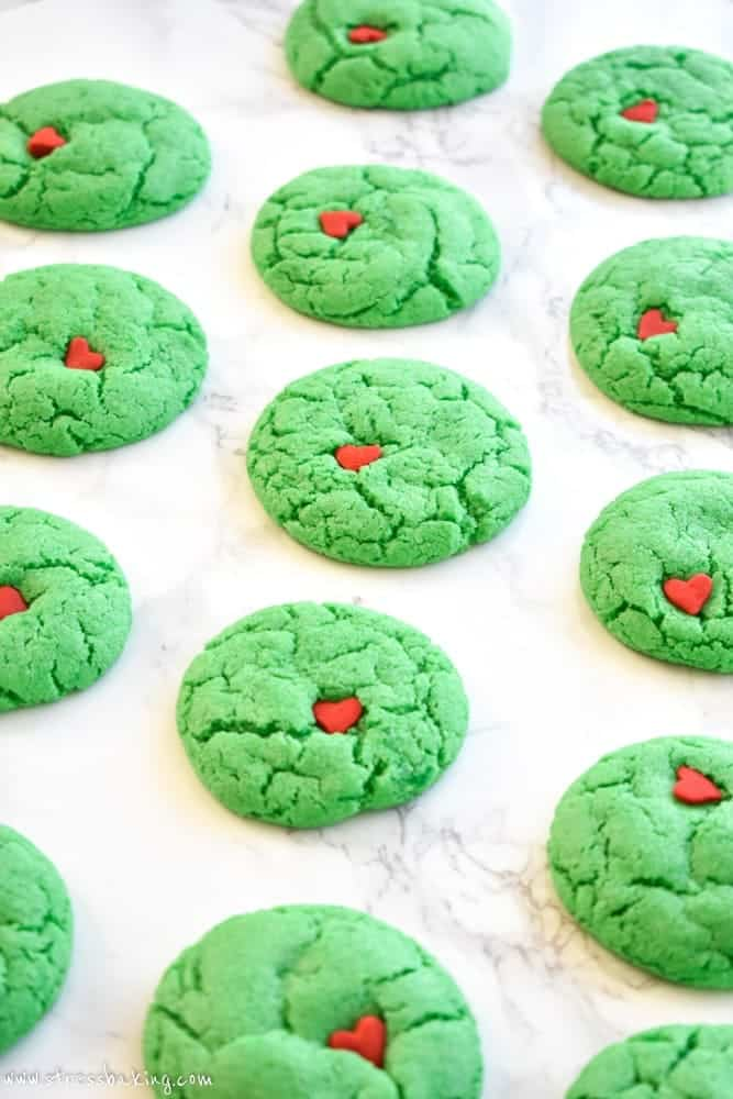Many rows of vibrant green Grinch cookies with red heart sprinkles