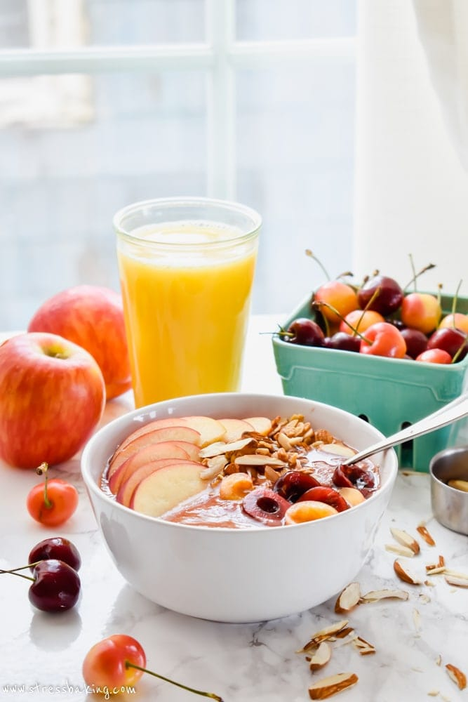 Apple Cherry Smoothie Bowl on a table with fresh fruit and orange juice