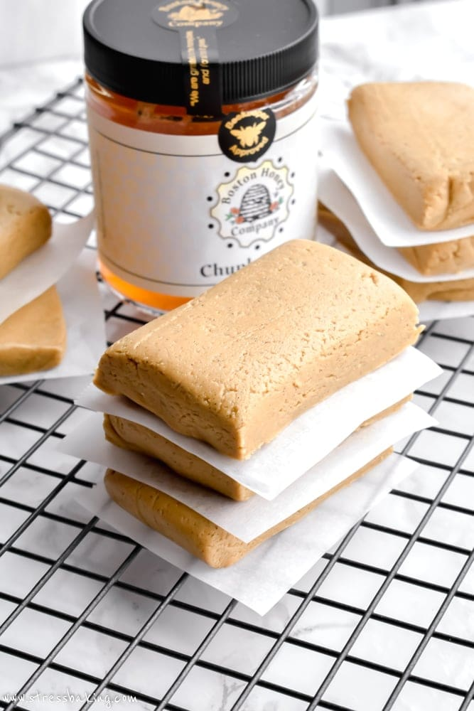 Chewy almond honey protein bars stacked between pieces of parchment paper on a wire rack with a jar of honey