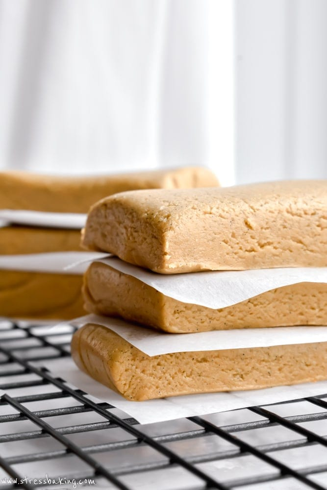 Side shot of chewy almond honey protein bars stacked between pieces of parchment paper on a wire rack