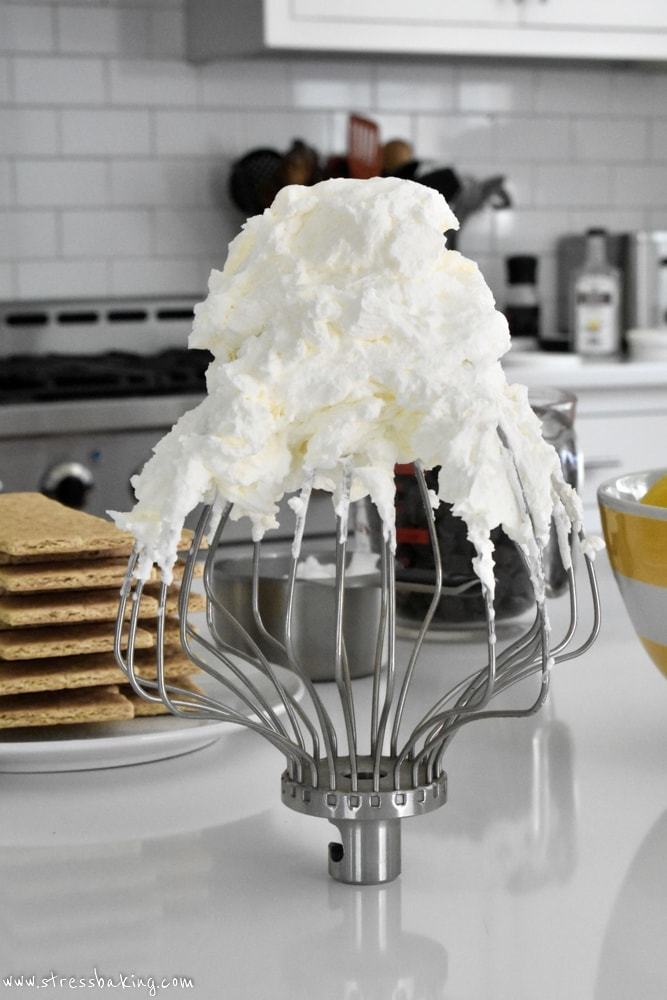 Mascarpone whipped cream on a whisk sitting on a kitchen counter