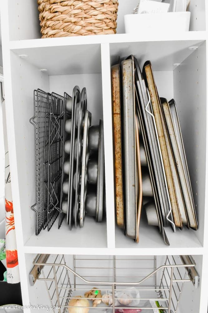 California Closets White pantry shelf holding baking sheets, muffin tins and cooling racks