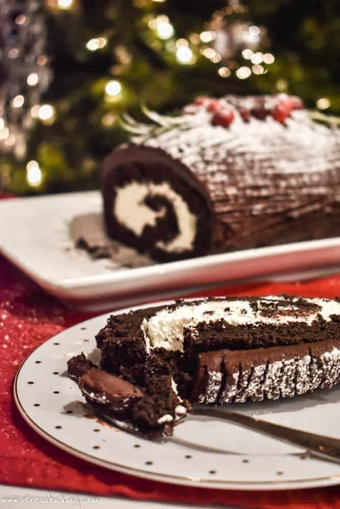 A slice of yule log cake in the foreground with the rest in the background in front of a Christmas tree