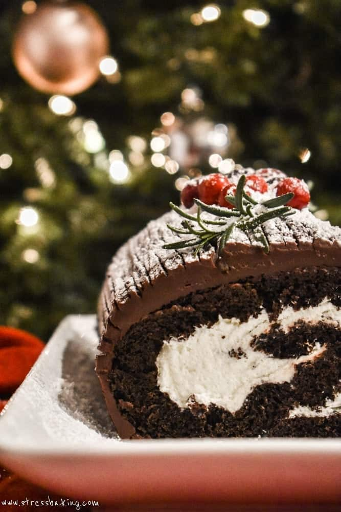 Yule log cake in front of a Christmas tree with a slice taken out to reveal the middle