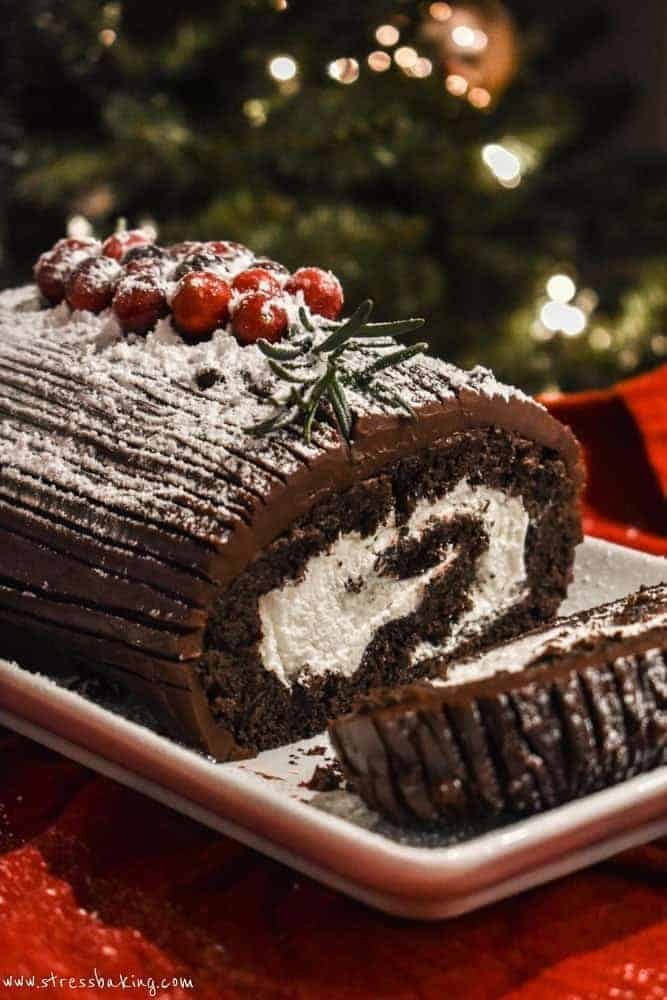 Yule Log Cake on a white platter with a slice on its side