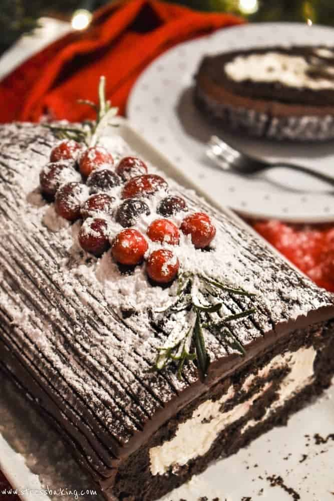 Yule log cake decorated with cranberries, powdered sugar, and rosemary sprigs