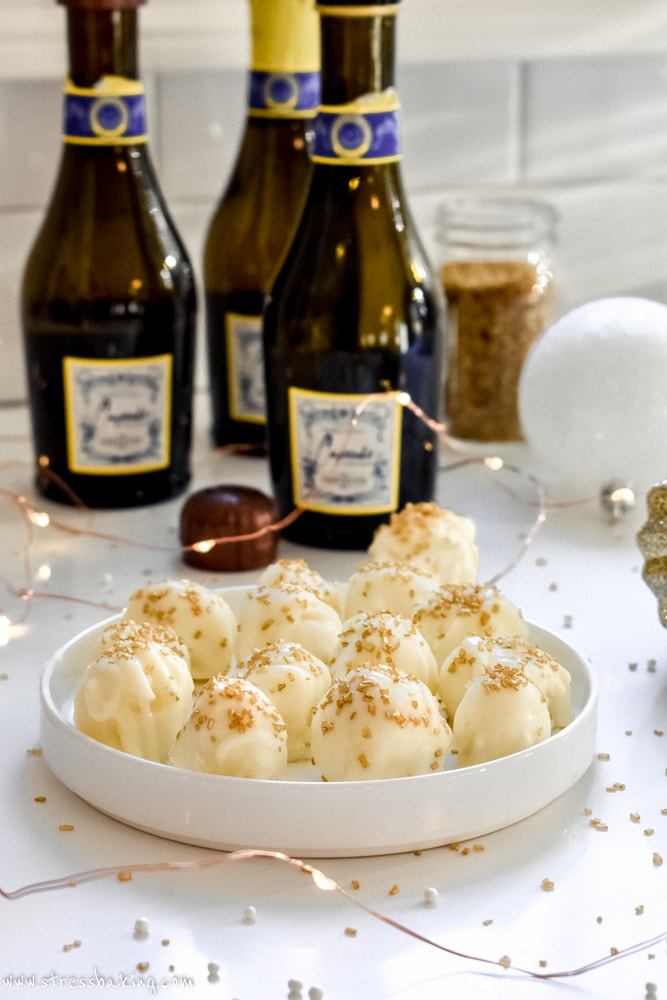 White Chocolate Champagne Truffles: Melt in your mouth white chocolate truffles are creamy with a delicate champagne flavor, making them the perfect dessert for your New Year's Eve party!   stressbaking.com @stressbaking #NYE #NewYearsEve #stressbaking #dessert #easyrecipe #whitechocolate #champagne #bubbly #bubbles #spiked