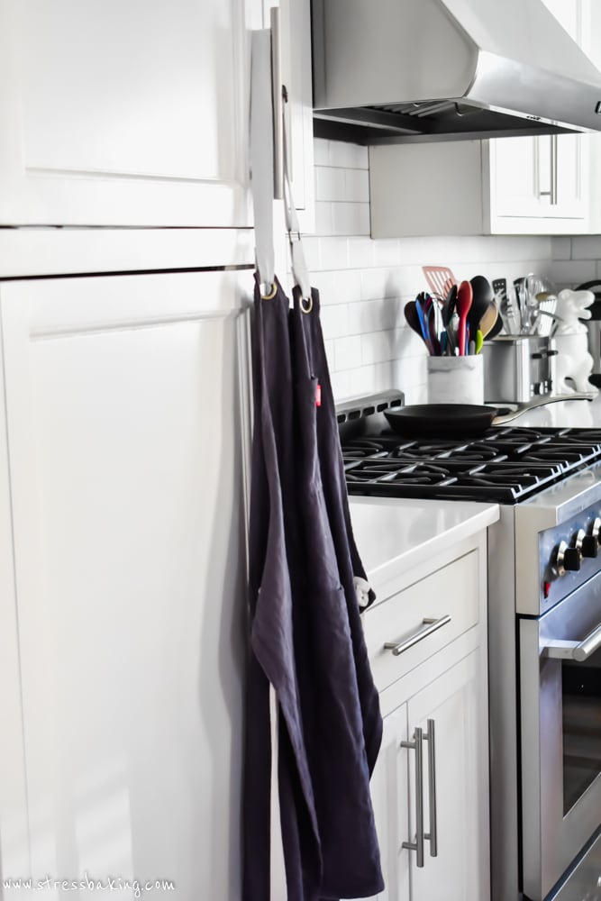 Dark blue kitchen apron hanging on a cabinet door