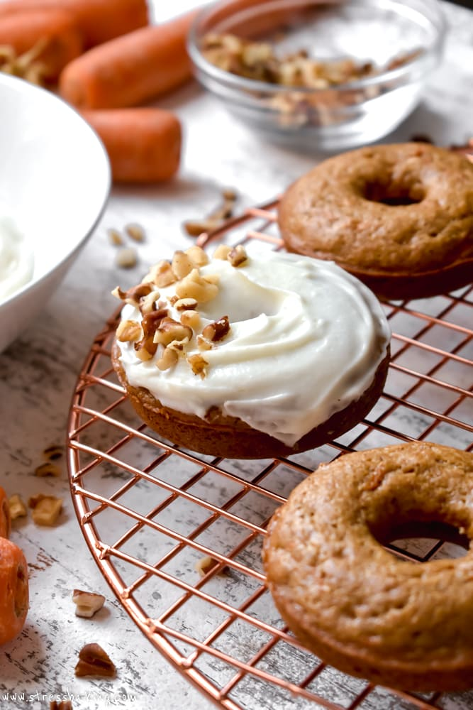 Carrot cake donuts topped with cream cheese icing and chopped nuts on a gold wire rack