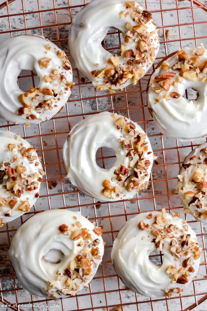 Overhead shot of carrot cake donuts topped with cream cheese icing and chopped nuts on a gold wire rack