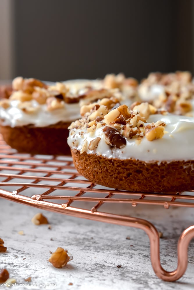 Side shot of carrot cake donuts topped with cream cheese icing and chopped nuts on a gold wire rack