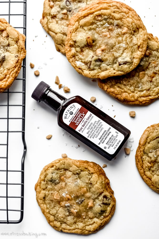 A bottle of Watkins Co. Vanilla extract in the middle of freshly baked cookies