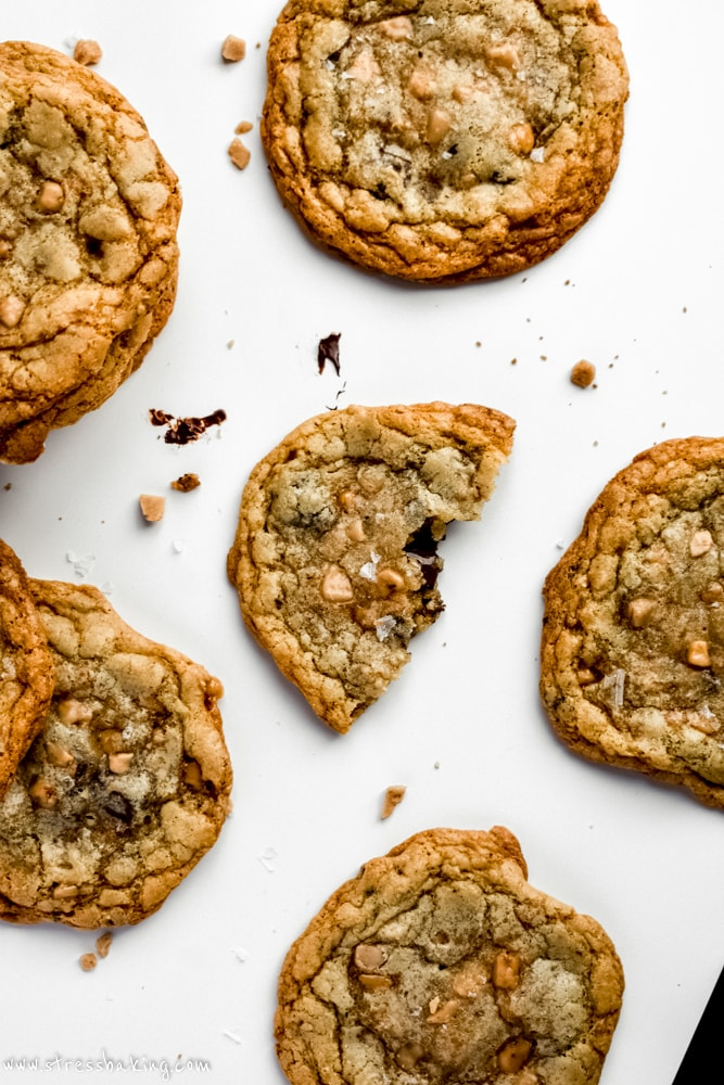 Salted Brown Butter Toffee Chocolate Chunk Cookies on a white counter with one torn in half